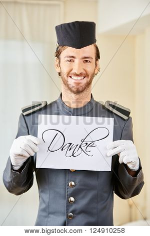Smiling hotel clerk holding German sign saying