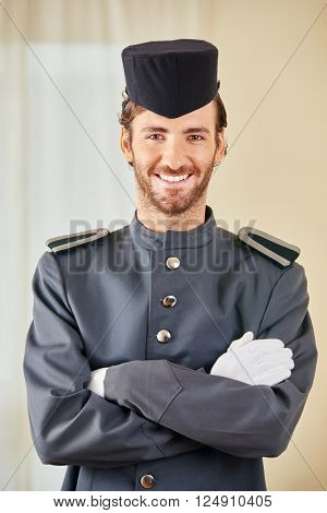 Friendly hotel page in uniform smiling in a hotel room