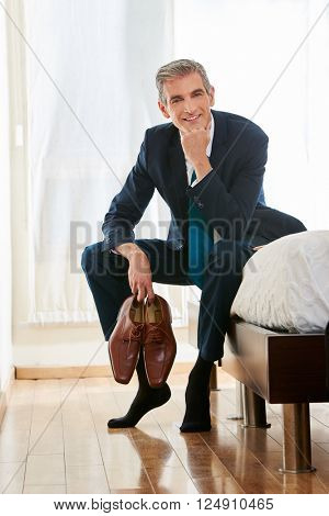 Smiling business man sitting with his shoes in his hands in a hotel room