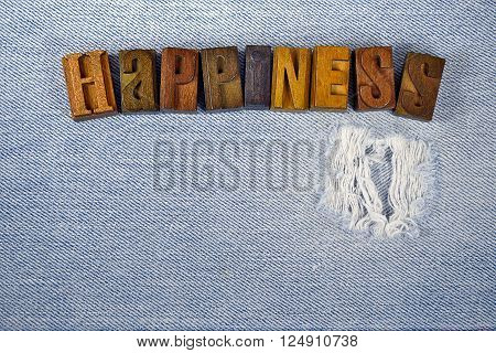 The word happiness in vintage wooden letterpress type on faded and frayed blue denim fabric.