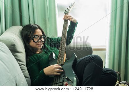 Happy cheeky girl,learning to play the Electric guitar at home laying on sofa