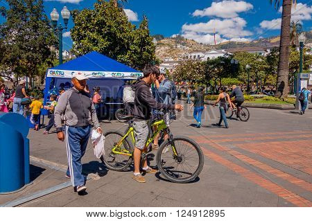 QUITO, ECUADOR - MARZO 23, 2015: Unidentified cyclist and men stop in the independence square of Quito to breath some fresh air and drink water in a nice day