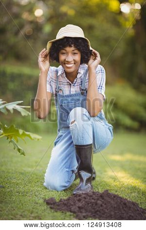 Smiling woman crouching in the garden holding her hat