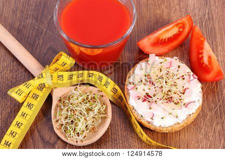 Freshly vegetarian sandwich with cottage cheese vegetables alfalfa and radish sprouts glass of tomato juice and tape measure slimming healthy lifestyle food and nutrition