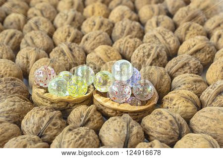 Walnuts background and two half nutshell in which contain some glass marbles.