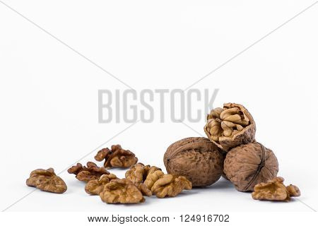 Two walnuts with a cracked walnut and kernels isolated on the white background.