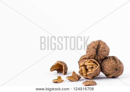 Walnuts and a cracked walnut with shells isolated on the white background