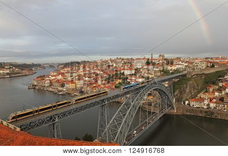 PORTO, PORTUGAL - November 27, 2014: View of the historic city of Porto with the Dom Luis bridge, metro train and rainbow at the background