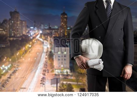 Close up of engineer hand holding white safety helmet for workers security standing in front of blurred urban background.