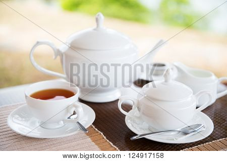 teatime, drink and object concept - close up of tea service on table at restaurant or teahouse