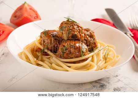 Meat balls in tomato sauce with pasta on a white background