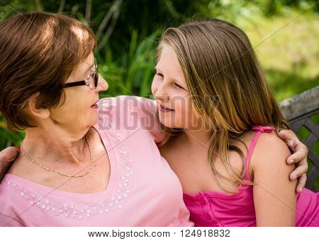 Portrait of grandchild with grandmother - outdoor in backyard