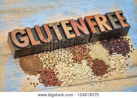 selection of gluten free grains (quinoa, rice, teff, buckwheat, sorghum,kaniwa, amaranth) and text in vintage letterpress wood type  against painted wood