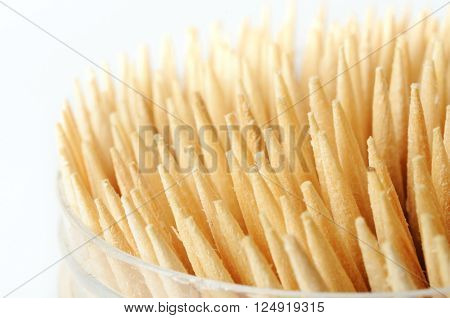 A glass with a bunch of wooden toothpicks. Close-up.