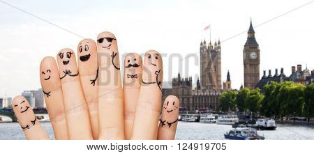 travel, tourism, family, people and body parts concept - close up of two hands showing fingers with smiley faces over london city background
