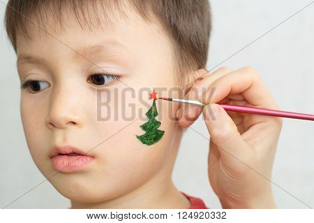 Painting  fir-tree on child face preparing for Christmas