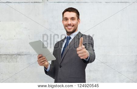 business, people, gesture and technology concept - smiling businessman with tablet pc computer showing thumbs up over gray concrete wall background