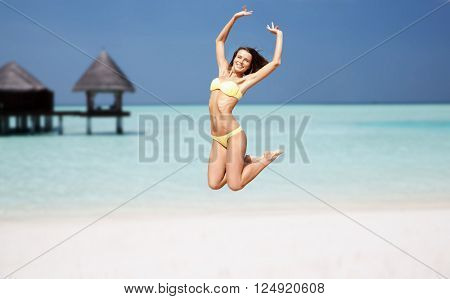 people, travel, tourism, summer vacation and holidays concept - happy young woman jumping over exotic maldives beach with bungalow background