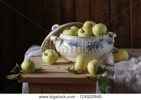 Still life in rustic style with apples in the soup tureen on the table.
