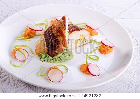 Chicken fillet wrapped in bacon stuffed with cheese and garnished with spring vegetables