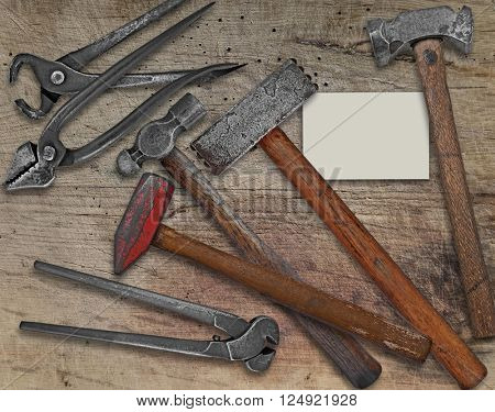 vintage blacksmith or metalwork tools over wooden bench,  business card for your text