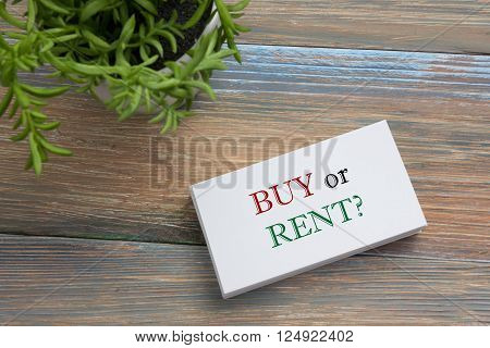 Real estate concept. Business card with buy or rent message and flower. Office supplies on desk table top view.