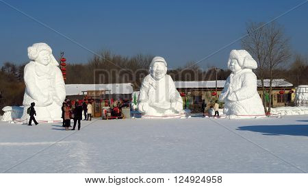 HARBIN CHINA - JANUARY 15 2016: people under snowy sculptures during the 32nd Harbin Ice Festival. The main attraction is the Harbin Ice and Snow World which covers more than 750000 square meters