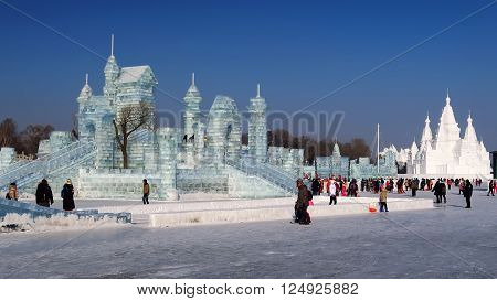 HARBIN CHINA - JANUARY 16 2016: people under a snowy castle during the 32nd Harbin Ice Festival. The main attraction is the Harbin Ice and Snow World which covers more than 750000 square meters.