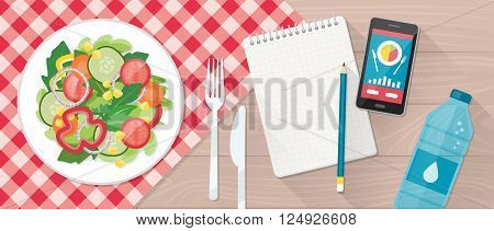Food diet healthy lifestyle and weight loss banner with a dish of salad table set smartphone and diet plan on a notebook