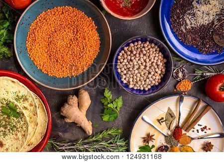 Table served with traditional for asian or eastern cuisine food. Cereal grains beans spices on colorful plates. Lentil basmati and wild rice mix chick-pea tomato chutney pita. Ingredients for indian or eastern food