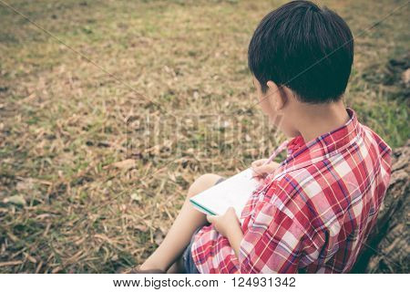 Boy Writing On Notebook. Education Concept. Vintage Style.