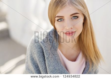 Beautiful woman with long blonde straight hair and grey eyes,plump lips,light makeup,dressed in a pink shirt and gray blazer,spends time alone on a city street,posing for the photographer,smiling sweetly