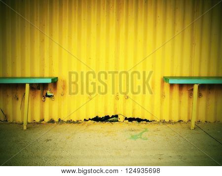 Old Wooden Sits On Outdoor Stadium Players Bench, Chairs Bellow Old Worn Yellow Roof.