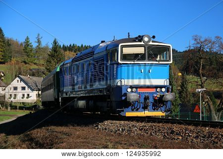 Diesel locomotive on the tracks passing through mountain landscape