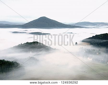 Fall Misty Valley Early Morning Within Sunrise. The Fog Is Moving Between Hills And Peaks Of Trees A