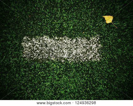 End Of Football Season. Dry Birch Leaf Fallen On Ground Of Plastic Green Football Turf With Painted