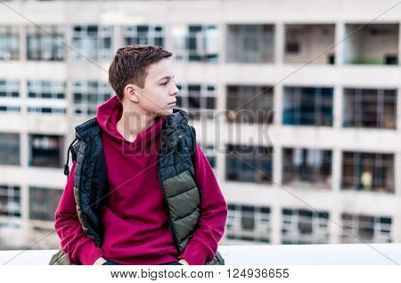 pensive teenager sitting on roof the house
