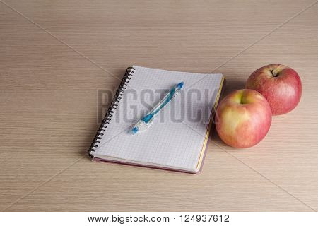 Notebook with apples fruit and pen on wooden table