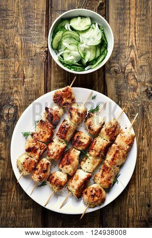 Chicken kebabs and cucumber salad on wooden background top view