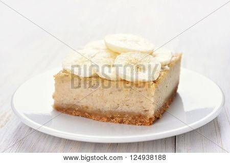 Banana cheese cake on white wooden table close up view