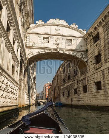 View of the Bridge of Sighs shot from within a gondola on a canal in Venice on a bright sunny day
