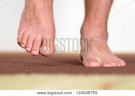 Healthy male feet stepping over home-like background ** Note: Shallow depth of field