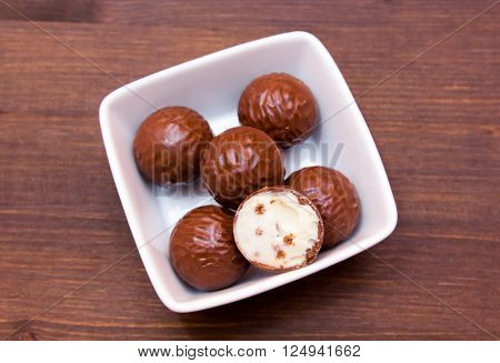 Chocolate pralines on a square bowl on wooden table top views
