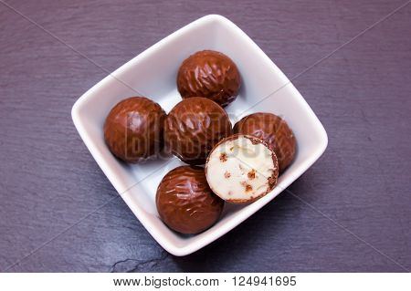 chocolate pralines on a square bowl on slate top top views