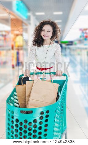 Happy girl with wavy curly hair with green shopping carts in the mall. Kraft bags with purchases. Make purchases with pleasure.