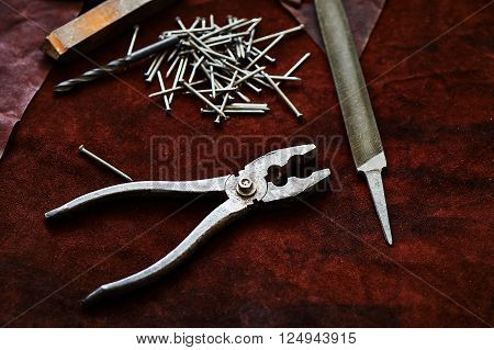 Set of tools on a piece of suede. Pliers, nails, a file, an old rusty piece of metal ** Note: Visible grain at 100%, best at smaller sizes