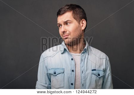 This is not a good idea! Young man looking away with irony while standing against grey background
