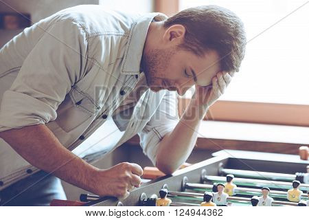 Looser. Desperate young man keeping his hand on forehead while standing over foosball in front of window