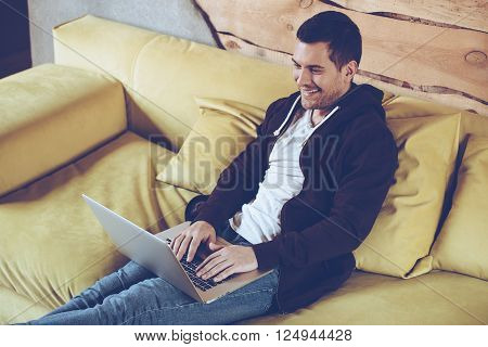 Surfing the net. Top view of cheerful young man using his laptop with smile while sitting on couch at home