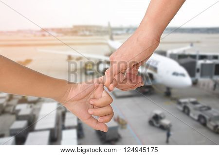 Closeup of mother holding her children hand with the airport background.